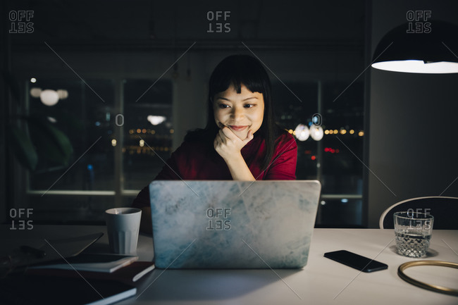 Confident businesswoman looking at laptop while sitting with hand on chin working late in office