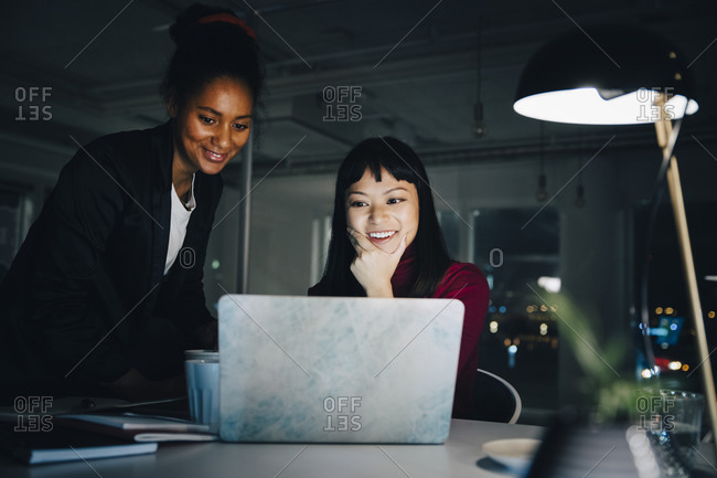 Smiling female entrepreneurs discussing while looking at laptop in creative office working late