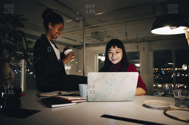 Happy female professionals working late during meeting in office