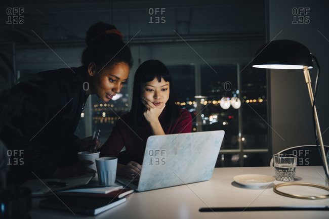 Confident businesswomen planning strategy while using laptop in night meeting at office