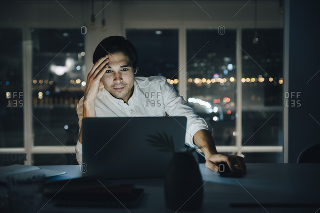 Businessman looking at laptop while working late in dark creative workplace