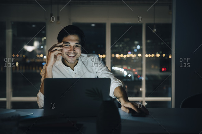 Smiling male professional working late while looking at laptop in dark coworking space