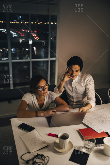 High angle view of female and male entrepreneurs sitting at desk during late night meeting in office