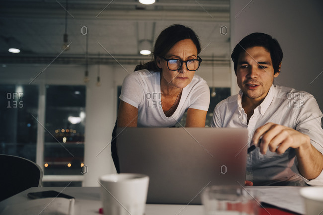 Confident businesswoman planning strategy with businessman during late night meeting at office