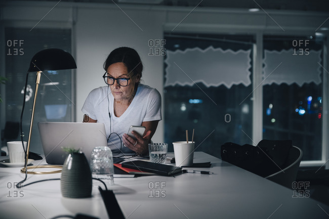 Confident mature female entrepreneur using laptop while sitting with smart phone at office