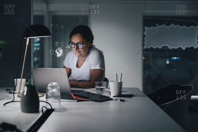 Confident businesswoman using laptop while working late night in office