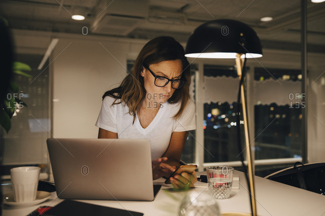Confident female entrepreneur using smart phone while sitting with laptop at illuminated desk in workplace during night