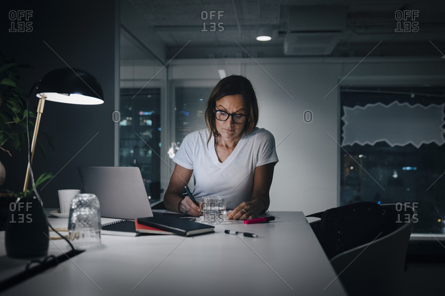 Female professional working late while sitting at desk in office
