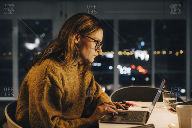 Ambitious businesswoman using laptop while working late at creative office
