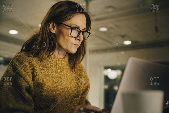 Determined mature female entrepreneur working late while using laptop at workplace