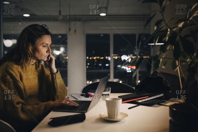 Side view of dedicated mature businesswoman using laptop while working late at creative office