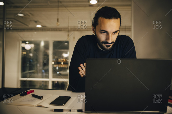 Confident businessman looking at laptop while working late in office