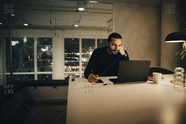 Tired businessman working late while sitting at desk in illuminated creative office
