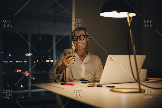 Smiling businesswoman using smart phone while sitting with laptop at illuminated desk in coworking space