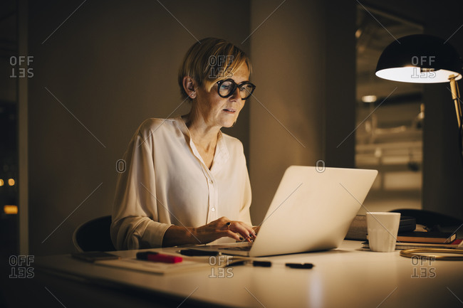 Determined businesswoman using laptop while working late in illuminated creative workplace