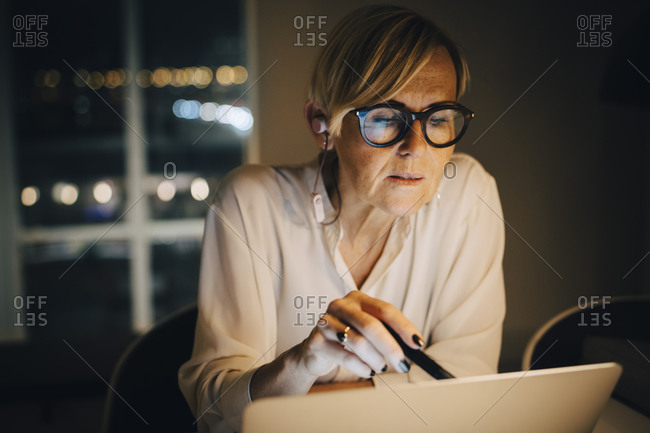 Dedicated mature female professional using laptop in illuminated office while working late