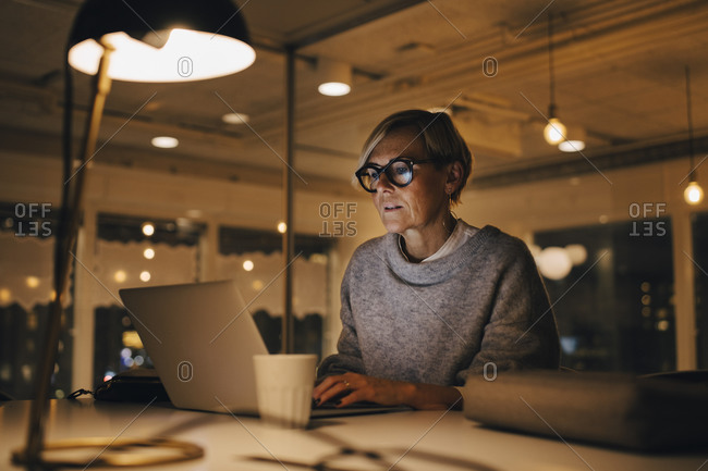 Confident mature female business professional using laptop while sitting at desk working late in office