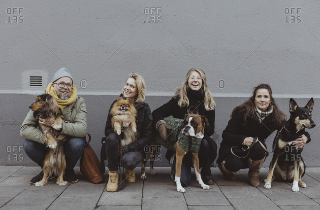 Portrait of smiling pet owners with dogs on footpath against wall in city
