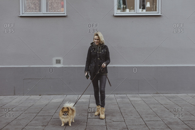 Full length of smiling woman standing with Pomeranian dog on footpath against building