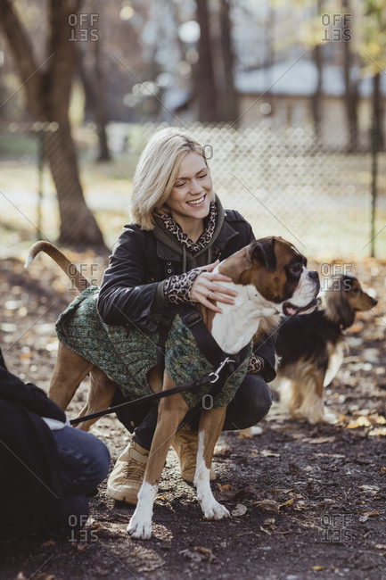 Smiling blond woman crouching by friend with dogs at park