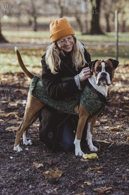 Smiling young woman looking at boxer dog while kneeling