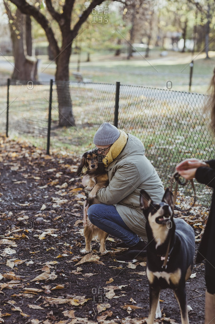 Side view of man crouching while embracing dog at park