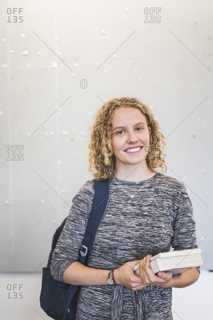 Portrait of confident female student standing against wall in university