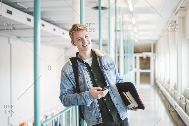 Portrait of happy young male student in corridor of university