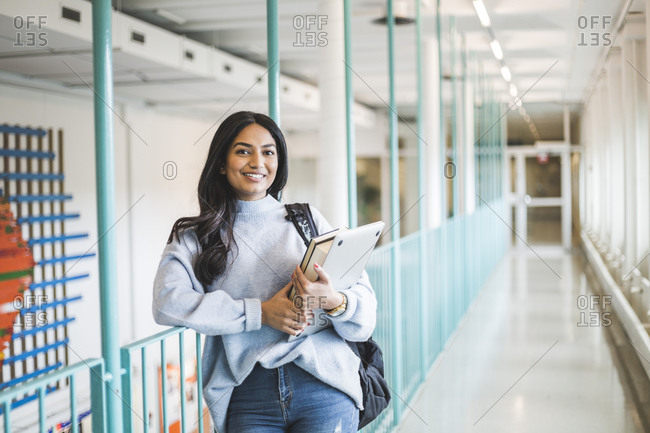 Portrait of young female student in corridor of university