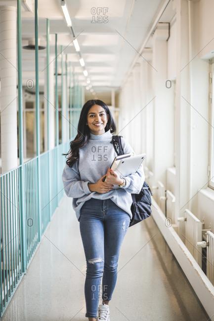 Portrait of young female student walking in corridor of university