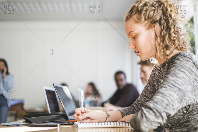 Young woman studying at desk in classroom