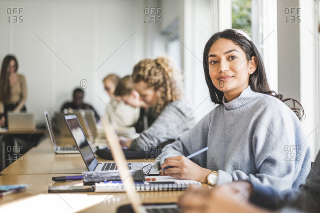 Portrait of confident young woman at desk in classroom
