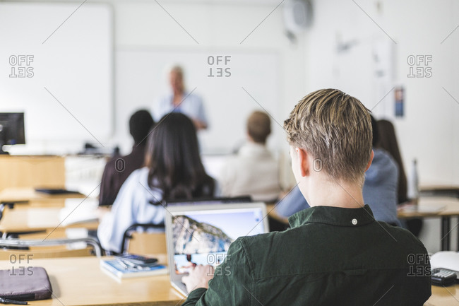 Cropped image of male student using laptop at desk in classroom