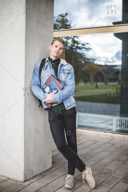 Portrait of confident university student leaning on wall