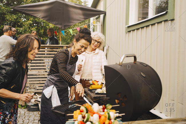 Smiling senior female friends barbecuing dinner at back yard during garden party