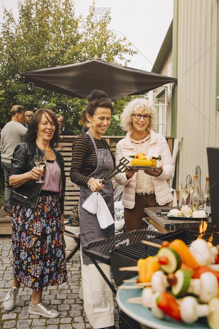 Happy elderly female friends preparing dinner on barbecue at back yard