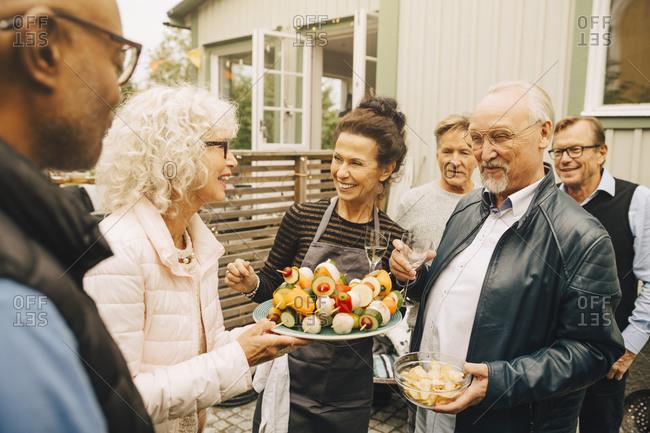Smiling senior women and men enjoying garden party