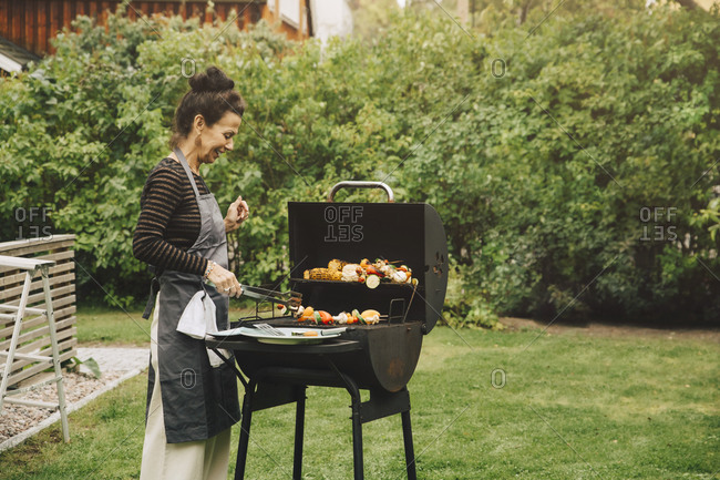 Side view of smiling woman cooking dinner on barbecue grill at back yard during garden party