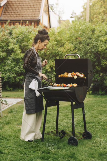 Full length side view of senior woman preparing meal on barbecue grill during dinner party at back yard