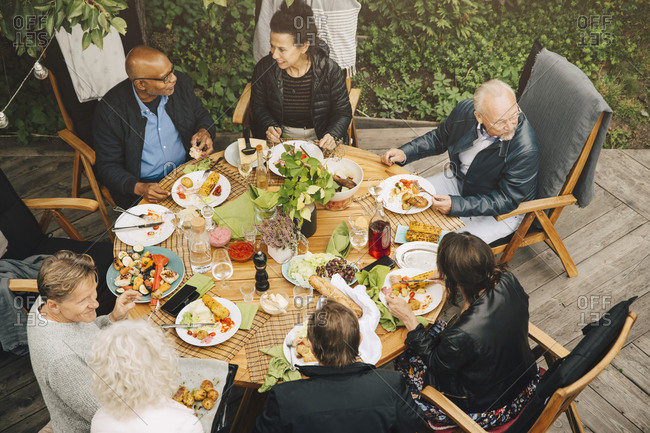 High angle view of senior friends enjoying meal at dining table during garden party at back yard