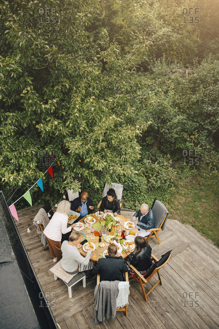 High angle view of senior woman serving friends sitting at dining table during garden party in back yard