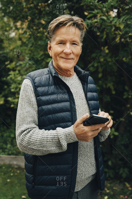 Portrait of smiling senior man holding smart phone while standing at back yard