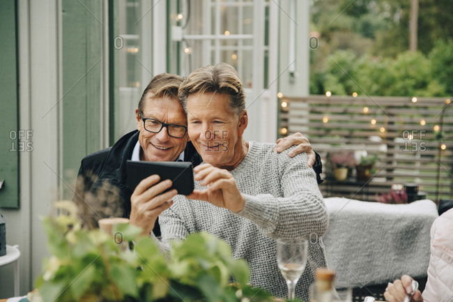 Smiling man showing smart phone with friend while sitting at back yard during party