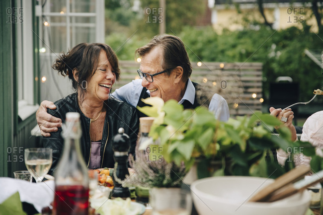 Smiling senior man and woman enjoying dinner party while sitting at dining table in back yard