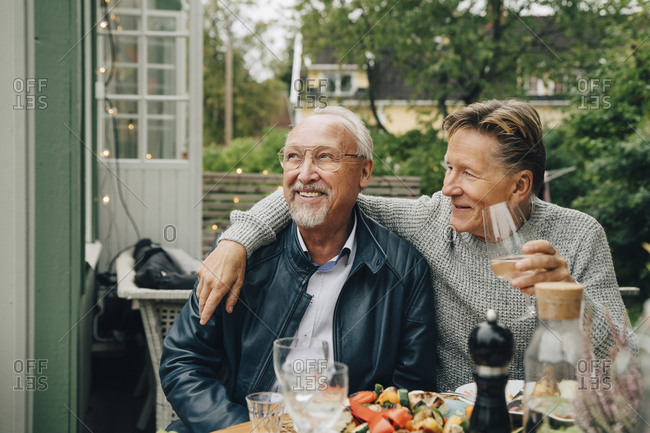 Smiling male friends sitting at dining table enjoying dinner party in back yard