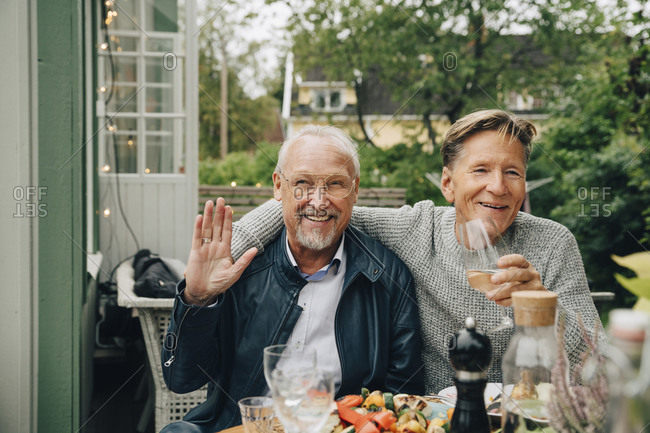 Happy male friends sitting at dining table enjoying dinner party in back yard
