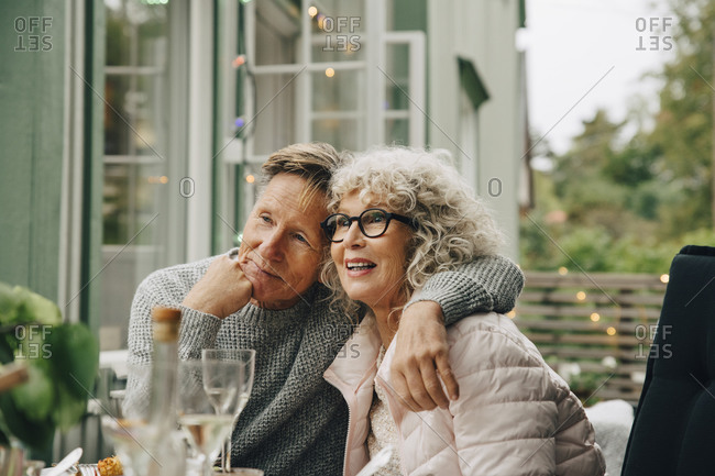 Thoughtful senior man sitting with arm around woman at dining table during garden party