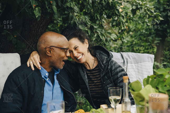 Cheerful senior man and woman enjoying while sitting at dinning table during garden party