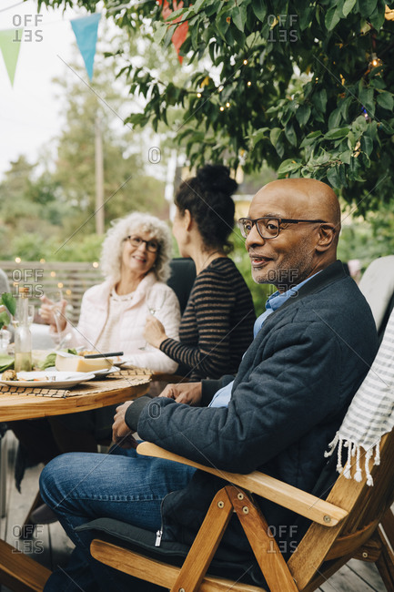 Smiling bald senior man sitting on chair enjoying dinner party by friends at back yard