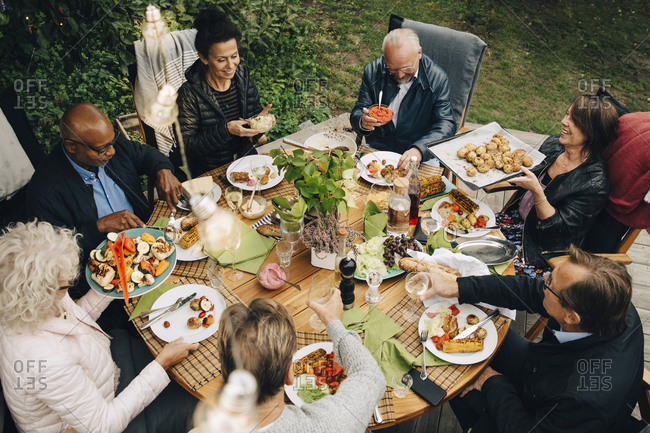 High angle view of senior male and female friends enjoying dinner at dining table during back yard garden party